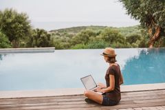 Young woman using laptop computer near swimming pool in hotel. Young woman using laptop computer in hotel. Freelance work and travel concept. People using royalty free stock photography