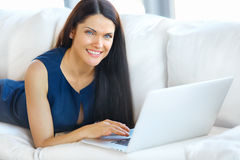 Young Woman Using a Laptop Computer While Relaxing at Home Royalty Free Stock Photography