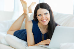 Young Woman Using a Laptop Computer While Relaxing at Home Stock Image