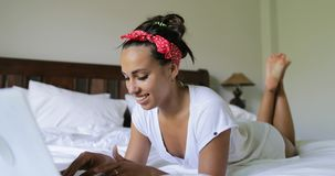 Young Woman Using Laptop Computer Typing Beautiful Girl Lying On Bed In Bedroom Morning. Slow Motion 60 stock footage