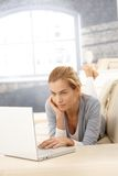 Young woman using laptop on couch Stock Images