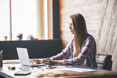 Young woman using laptop. On desktop with various items in interior Royalty Free Stock Photography