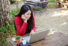 Young woman using laptop and drinking coffee in garden stock photo
