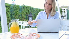 Young woman using laptop and eating pizza sitting in cafe in city.  stock footage