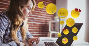 Young woman using laptop while emojis flying over. Digital composite of Young woman using laptop while emojis flying over Stock Photography