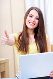 Young woman using laptop and giving thumbs-up Royalty Free Stock Image