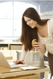Young woman using laptop having croissant Royalty Free Stock Images