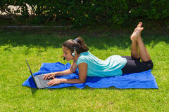 Young woman using a laptop and headphones outdoors. Stock Photo