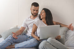 Young woman using laptop while her dissatisfied boyfriend gesturing in bed Royalty Free Stock Photo