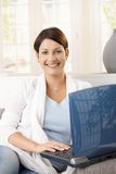 Young woman using laptop at home Stock Images
