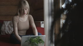 Young woman using a laptop at home. Young pensive woman sitting on the couch while typing and reading emails on the laptop with winter background on the window stock footage