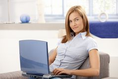 Young woman using laptop at home smiling royalty free stock image