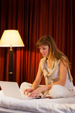 Young woman using laptop in hotel Stock Photos