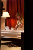 Young woman using laptop in hotel Stock Photography