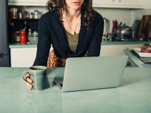 Young woman using laptop in kitchen. A young woman is using her laptop in a kitchen and is having a cup of coffee Stock Photo
