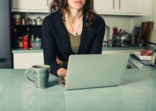 Young woman using laptop in kitchen. A young woman is using her laptop in a kitchen and is having a cup of coffee Royalty Free Stock Photography