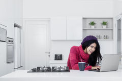 Young woman using laptop in kitchen. Portrait of beautiful woman using a laptop while sitting in the kitchen with hot coffee Royalty Free Stock Photos