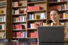 Young woman Using Laptop In Library Royalty Free Stock Photo