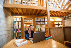 Young woman using laptop in library. At college Royalty Free Stock Photography