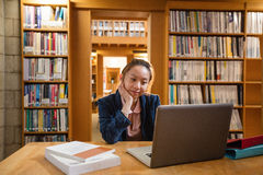 Young woman using laptop in library Royalty Free Stock Images
