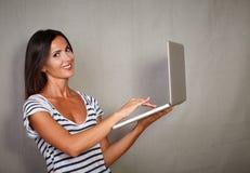 Young woman using laptop while looking at camera Royalty Free Stock Photos