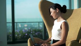 Young woman using laptop and looking to camera stock footage