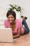 Young woman using laptop while lying on floor at home. Stock Photo