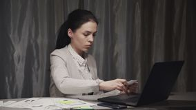 Young woman using laptop and making notes. Smart and successful young caucasian woman in formal wear suit, working inside home office, sitting behind table and stock video
