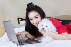 Young woman using a laptop with Maltese dog. Portrait of pretty young woman with Maltese puppy lying on the bed while using a laptop computer and looking at the Royalty Free Stock Photos