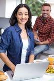 Young woman using laptop and man using digital tablet Stock Photos