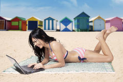 Young woman using a laptop on mat. Beautiful young woman using a laptop and lying on mat with background of the beach huts Stock Image
