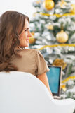 Young woman using laptop near christmas tree Royalty Free Stock Image