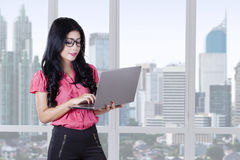 Young woman using laptop in office Stock Image