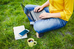 Young woman using laptop outdoor. Young woman using laptop while sitting in a park Stock Photo