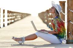 Young woman using laptop outdoor in summer. Young smiling woman using laptop outdoor in summer Royalty Free Stock Photo