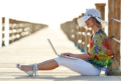 Young woman using laptop outdoor in summer Royalty Free Stock Image