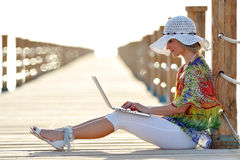Young woman using laptop outdoor in summer. Sunny day Stock Photography