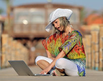Young woman using laptop outdoor in summer Stock Images