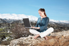 Young woman using laptop outdoors Stock Photo