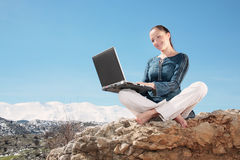 Young woman using laptop outdoors Stock Photos