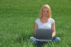 Young woman using laptop outside. Attractive young woman using laptop using laptop outside on green meadow Royalty Free Stock Images