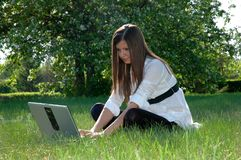 Young woman using laptop in park Stock Photo