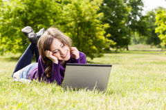Young woman using laptop in the park Royalty Free Stock Photos