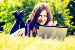 Young woman using laptop in the park lying on the green grass. Leisure time activity concept Stock Images