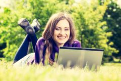 Young woman using laptop in the park lying on the green grass Royalty Free Stock Photography