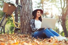 Young woman is using laptop in a park on a sunny autumn day Royalty Free Stock Image