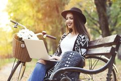 Young woman is using laptop in a park on a sunny autumn day Royalty Free Stock Photos