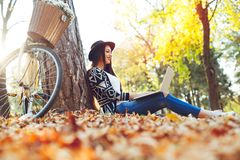 Young woman is using laptop in a park on a sunny autumn day Stock Photos