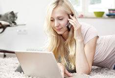 Young woman using Laptop and phone Stock Image