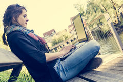 Young woman using laptop at a riverbank. Stock Photos